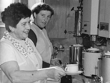 Zwei Frauen in Arbeitskitteln stehen vor zwei großen Kaffeemaschinen und bieten jemandem eine Tasse Kaffee an