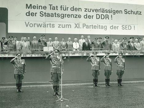 Vor dem Podium sind fünf Soldaten in Uniform zum militärischen Gruß aufgestellt. Vor dem zweiten Soldaten von links steht ein Mikrofon. Auf der Tribüne befinden sich mehrere Männer in ziviler Kleidung und in Uniform sowie eine Frau. Über den Personen auf der Tribüne steht 'Meine Tat für den zuverlässigen Schutz der Staatsgrenze der DDR! Vorwärts zum XI. Parteitag der SED!'.