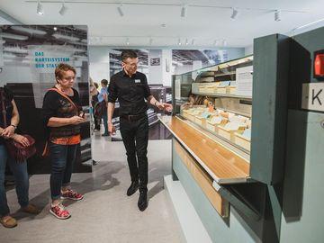 EIn Führer erklärt etwas an einem Karteiumlaufschrank in der Ausstellung.