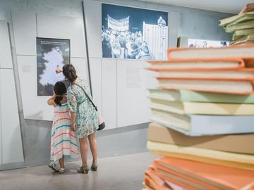 A recreated pile of files is in the centre of one of the exhibition rooms. In the background you see a woman with a child who use the touchscreen.