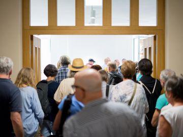 Viele Menschen drängen in einen Ausstellungsraum.