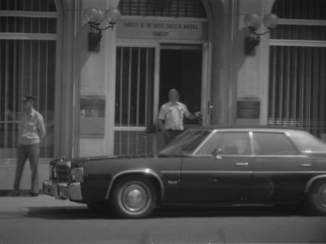 Observationsfoto der Stasi vom Eingang der amerikanischen Botschaft in Ost-Berlin. Im Vordergrund ist ein US-PKW abgebildet. Ein Mann tritt gerade aus der Tür der Botschaft. Am linken Bildrand patrouilliert ein Polizist.