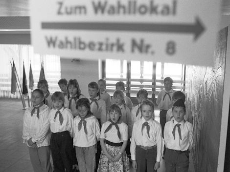Ein Kinderchor empfängt die Bürgerinnen und Bürger in einem Wahllokal.