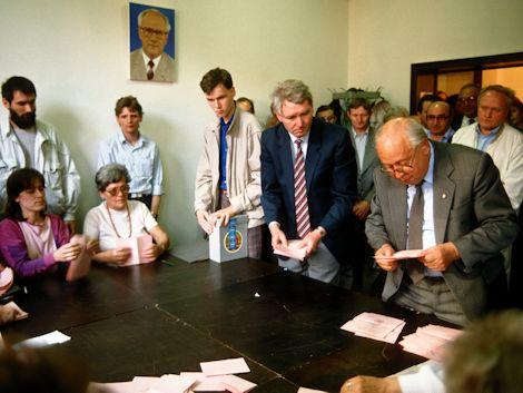 Ein Mann wertet einen Stimmzettel aus. Um ihn herum sind viele Menschen, die ihn beobachten.