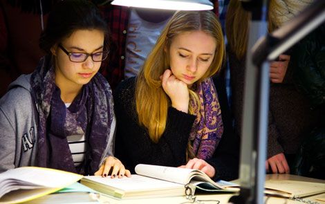 Two pupils reading sample files in the Stasi Records Agency.