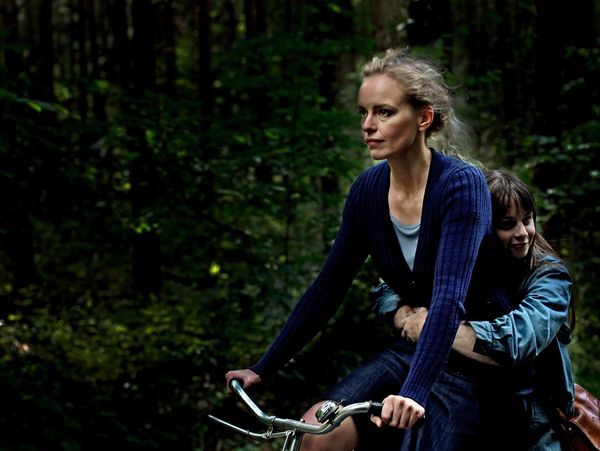 Film scene from the movie 'Barbara'. A woman and a girl are driving a bicycle.