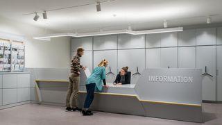 Eine Besucherin und ein Besucher stehen an einem Informationstresen und sind im Gespräch mit einer Mitarbeiterin.