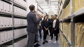 Das Bild zeigt einen Besucherreferenten, der mit einer Gruppe eine Führung in einem Magazinraum im Stasi-Unterlagen-Archiv macht.
