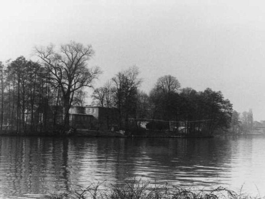 Aufgenommen vom gegenüberliegenden Ufer des Gewässers ist das Haus kaum zwischen den zahlreichen, überwiegend kahlen Bäumen auszumachen. Es handelt sich um ein schwarz-weißes Lichtbild.