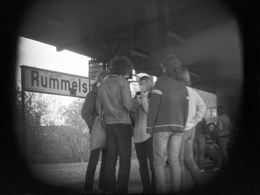 Das schwarz-weiße Negativ zeigt in der Bildmitte fünf Personen, die gesprächig in einer Runde zusammenstehen. Sie befinden sich auf dem Bahnhof Berlin-Rummelsburg, was anteilig am Stationsschild hinter ihnen zu lesen ist. Im Hintergrund ist eine weitere Personengruppe zu sehen, die sich überwiegend auf die Sitzplätze niedergelassen haben. Aufgrund der verdeckten Bildaufnahme wirkt der Bildfokus rund, die Ecken sind schwarz.