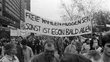 Blick auf einen Demonstrationszug am Berliner Alexanderplatz. Im Vordergrund sind einzelne Gesichter zu erkennen, dahinter tragen mehrere Personen ein großes Transparent mit der Losung: 'Freie Wahlen müssen sein, sonst ist Egon bald allein'.