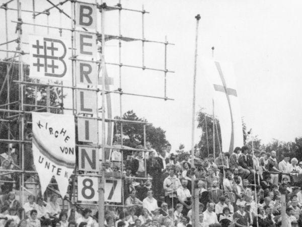 [Das schwarzweißbild zeigt zahlreiche Personen auf einer Tribüne im Stadion. Auf ein Stangengerüst ist das Logo des Kirchentages sowie 'Berlin 87' mit Buchstabentafeln senkrecht angebracht. Daneben ist ein offensichtlich selbstgemaltes Transparent der 'Kirche von unten' befetigt.]