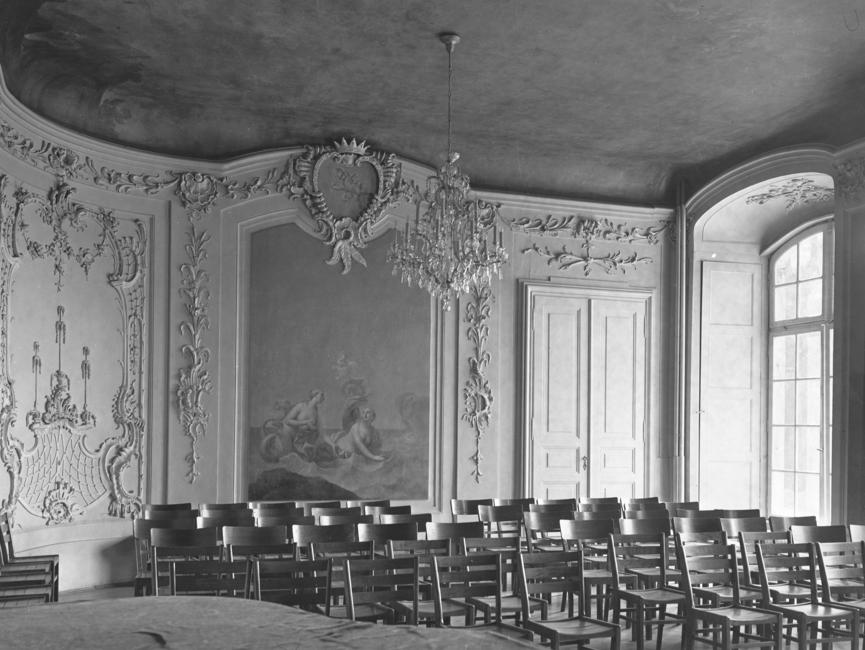 Das schwarz-weiße Lichtbild wurde in dem 'Gartensaal' des Schloss Nischwitz, Gemeinde Thalwitz, aufgenommen. Der durch zwei Wandgemälde geschmückte Saal, im Stil des spätbarock mit Stuck versehen, ist bestuhlt. Auf der rechten Wandseite ist ein Bodentiefes Fenster. Es handelt sich um ein schwarz-weißes Lichtbild.