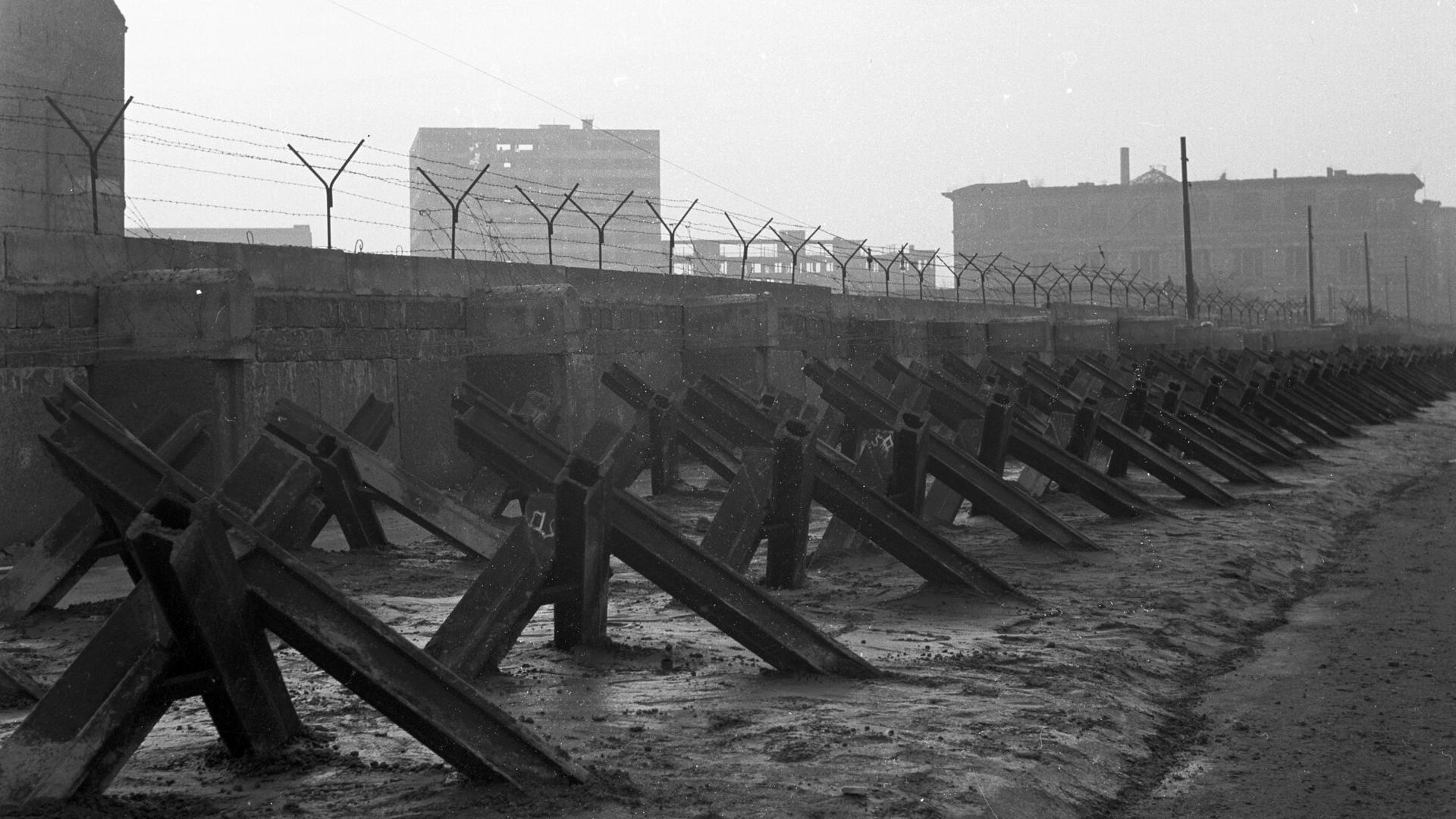 Das Schwarz-Weiß-Foto zeigt den Grenzverlauf in Berlin-Mitte unmittelbar nach dem Mauerbau. Das Bild zeigt eine Mauer mit aufgesetztem Stacheldraht und Panzersperren im Vordergrund.