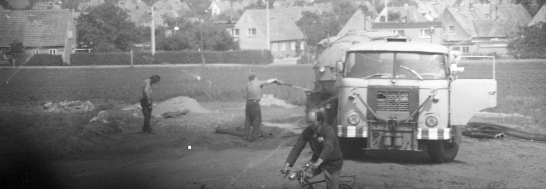 [Zu sehen sind auf dem Schwarzweißfoto zwei Personen auf einer vermutlichen Baustelle, rechts von ihnen steht vermutlich ein IFA W50. Bei dem hellen Lastkraftwagen steht die Tür offen. Im Vordergrund fährt ein Mann auf einem Fahrrad. Im Bildhintergrund erstreckt sich ein Dorf oder eine Kleinstadt, überwiegend aus Einfamilienhäusern bestehend.]