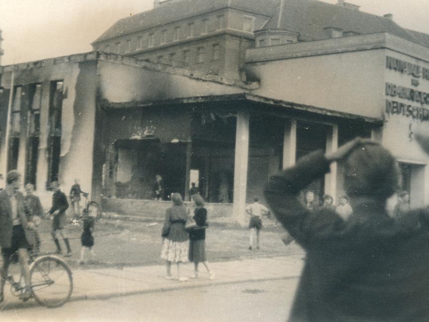 Menschen vor dem ausgebrannten Pavillon der Nationalen Front auf dem Leipziger Marktplatz.