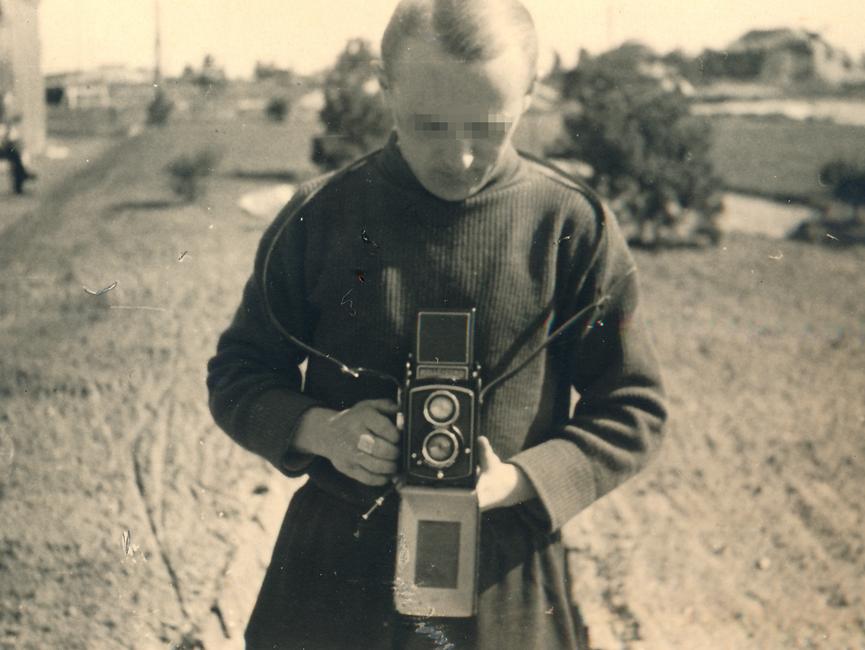 Das schwarz-weiße Lichtbild zeigt einen blonden Fotografen, die Frontalaufnahme geht bis über die Hüfte. Er blickt nach unten auf seine Kamera, im Hintergrund erstreckt sich eine weite Landschaft mit wenigen kleinen Bäumen.