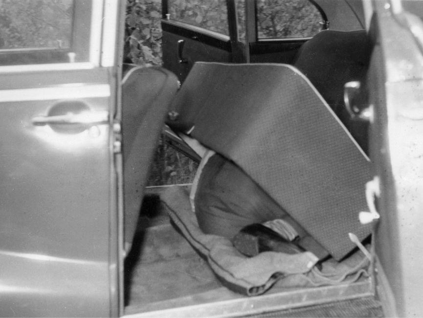 Zu sehen ist eine Person, die sich zusammengerollt unter einem hohlen Sitz in der Rückbank eines Pkw versteckt.