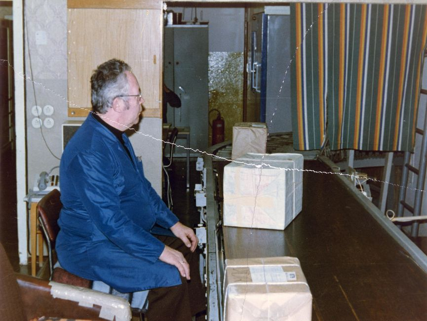 Das Bild zeigt einen Mann in einem blauen Arbeitskittel, der auf ein Förderband schaut, auf dem Pakete transportiert werden.