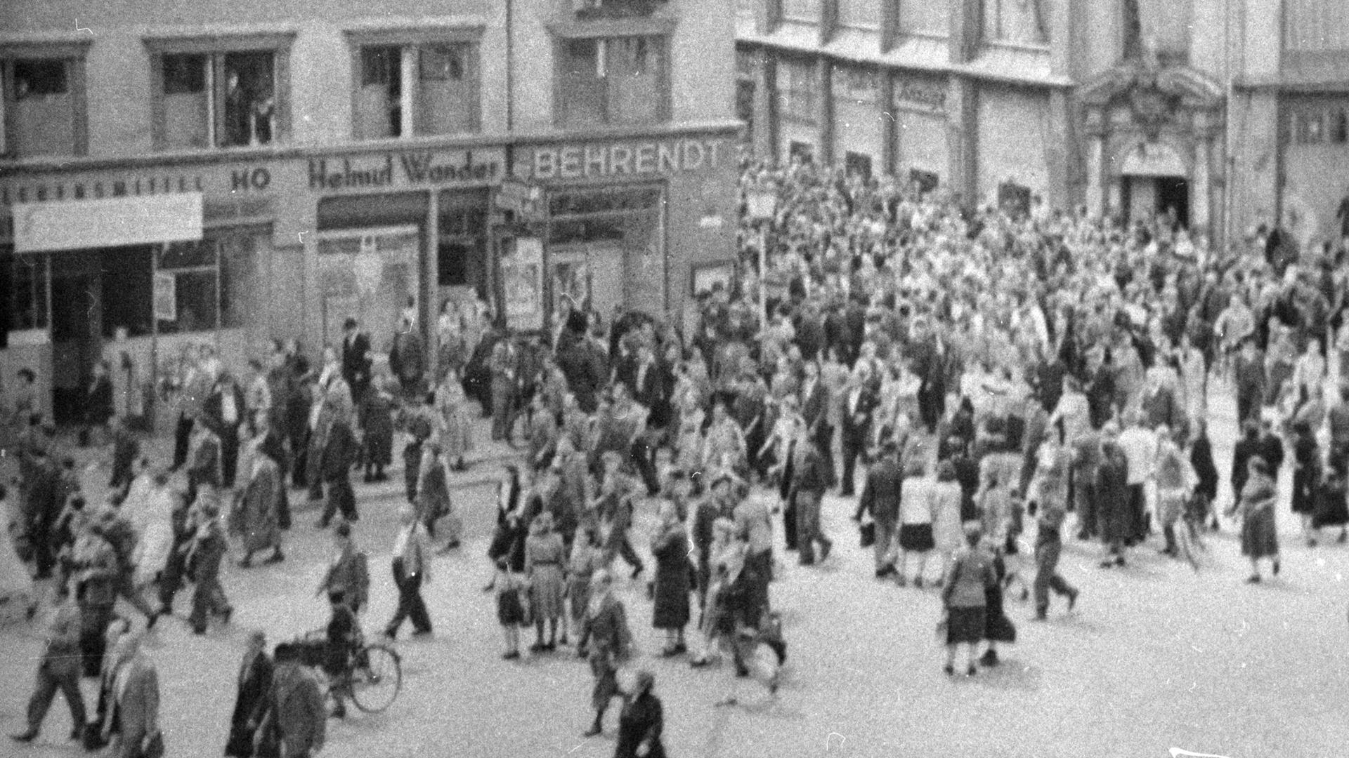 DAs Schwarz-Weiß-Bild zeigt eine Menschenansammlung auf einer Straße. In den Häusern an der Straße sind verschiedene Geschäftee ansässig.