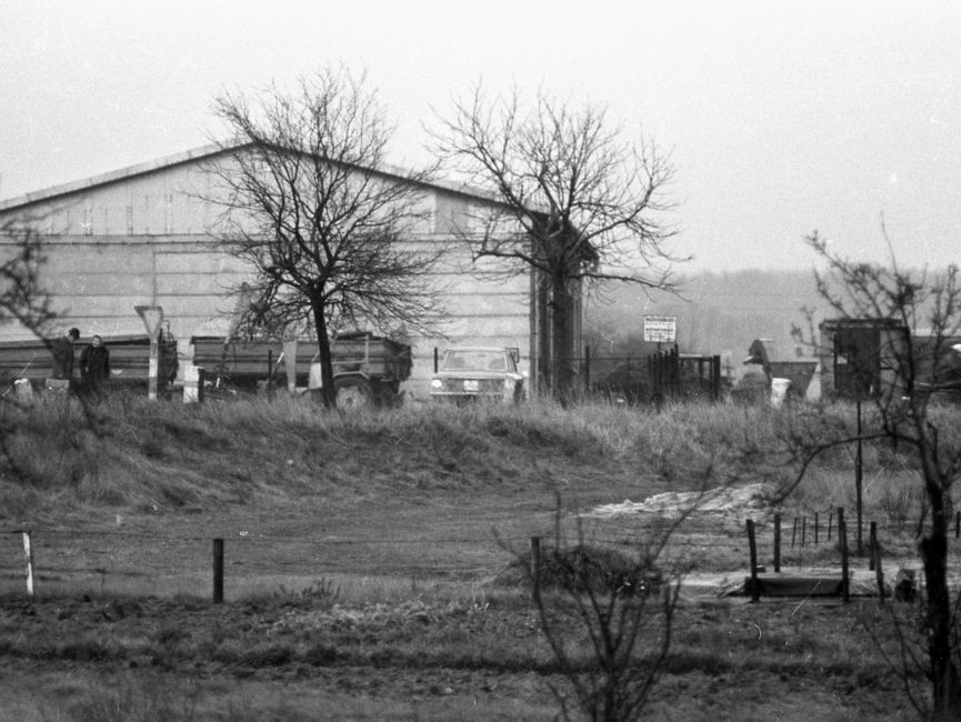 [Vor der Stirnseite eines langen Flachbaus stehen zwei Anhänger für Lastkraftwagen. Auf dem eingezäunten Hof rechts an dem Flachbau stehen diverse große Gegenstände, die nicht weiter erkennbar sind. Die Bäume am Straßenrand sind kahl. Es handelt sich um ein schwarzweißes Lichtbild.]