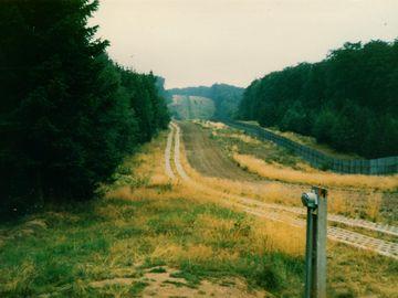 Zu sehen ist ein Blick entlang der Grenzsicherungsanlagen der DDR. Nach einem zweispurigen Weg aus Betongittern grenzt eine geharkte Sandfläche an. Vor dem Grenzzaun ist ein ungepflegt wirkender Abschnitt mit einigen hohen Gräsern. Auf der BRD-Seite grenzt Wald.