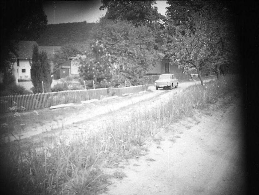 Zu sehen ist eine Siedlung auf der linken Seite, davor liegt eine unbefestigte, zweispurige Straße. Am Rand wurde ein Wartburg abgeparkt. Es handelt sich um ein schwarz-weißes Lichtbild. Die Ecken sind abgedunkelt, vermutlich wurde das Foto verdeckt aufgenommen.