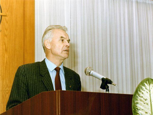 Hans Modrow steht an einem Pult und hält eine Rede. Vor ihm ragt das Blatt einer Pflanze ins Bild.