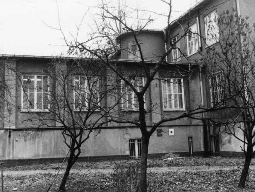 Hinter drei kleinen kahlen Laubbäumen ist die Fensterfront des Anbaus nebst Übergang ins Haupthaus zu sehen. Es handelt sich um ein schwarz-weißes Lichtbild.