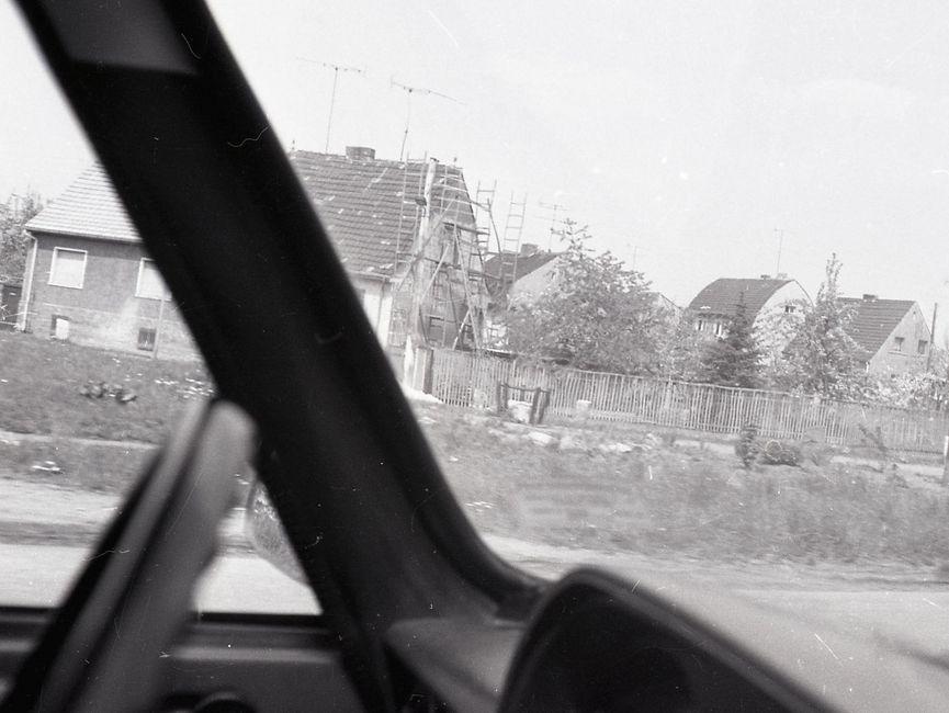 [Die schwarz-weiß Fotografie wurde durch die Windschutzscheibe eines Fahrzeugs von der Beifahrerseite über das Lenkrad hinweg aufgenommen. Auf der Fotografie sind im Hintergrund Einfamilienhäuser zu sehen. Links ist ein Einfamilienhaus mit Baugerüst zu erkennen. Rechts am Rand des Bildes ist ein parkendes Transportfahrzeug mit Beifahrer zu erkennen.]
