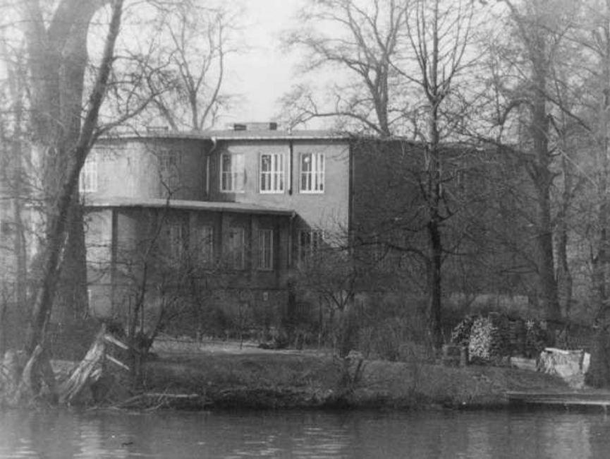 Das schwarz-weiße Lichtbild zeigt ein Gebäude mit Flachdach, das umgeben ist von kahlen Laubbäumen und dicht am Ufer eines Gewässers ist, welches im Bildvordergrund zu sehen ist.