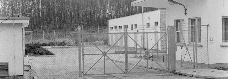 [Den Bildmittelpunkt des schwarz-weißen Lichtbilds zeigt die verschlossene Einfahrt des umzäunten Geländes. Der WEg zum Bungalow ist durch Beton geebenet. Im Hintergrund ist ein Funkmast erkennbar.]
