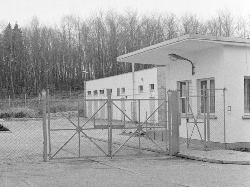Den Bildmittelpunkt des schwarz-weißen Lichtbilds zeigt die verschlossene Einfahrt des umzäunten Geländes. Der WEg zum Bungalow ist durch Beton geebenet. Im Hintergrund ist ein Funkmast erkennbar.