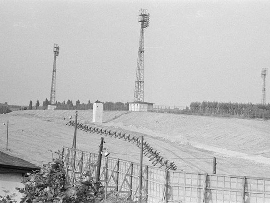 Das schwarz-weiße Lichtbild zeigt die Sicherungsanlagen der innerdeutschen Grenze. Auf einem Hügel stehen im Hintergrund drei Funktürme, die umzäunt sind.