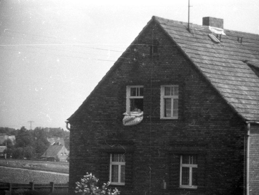 [Blick auf die Stirnseite eines zweistöckigen Backsteinhauses: eine Person lehnt sich auf eine Bettdecke, die leicht aus dem linken Giebelfenster vermutlich zum Lüften hängt. Im Hintergrund sind diverse Einfamilienhäuser zu sehen. Es handelt sich um ein  schwarzweißes Lichtbild.]