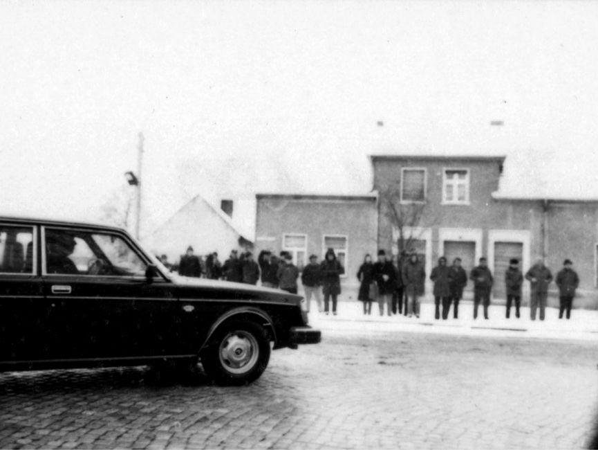 Auf der Schwarzweißaufnahme sind nur einige wenige Zuschauer an der Protokollstrecke in Güstrow während Helmut Schmidts Staatsbesuchs in der DDR, zu sehen. Hinter den Zuschauern ist ein kleines Wohnhaus. Auch hier liegt Schnee. Am linken Bildrand ist ein Auto, das nach rechts einbiegt zu erkennen.