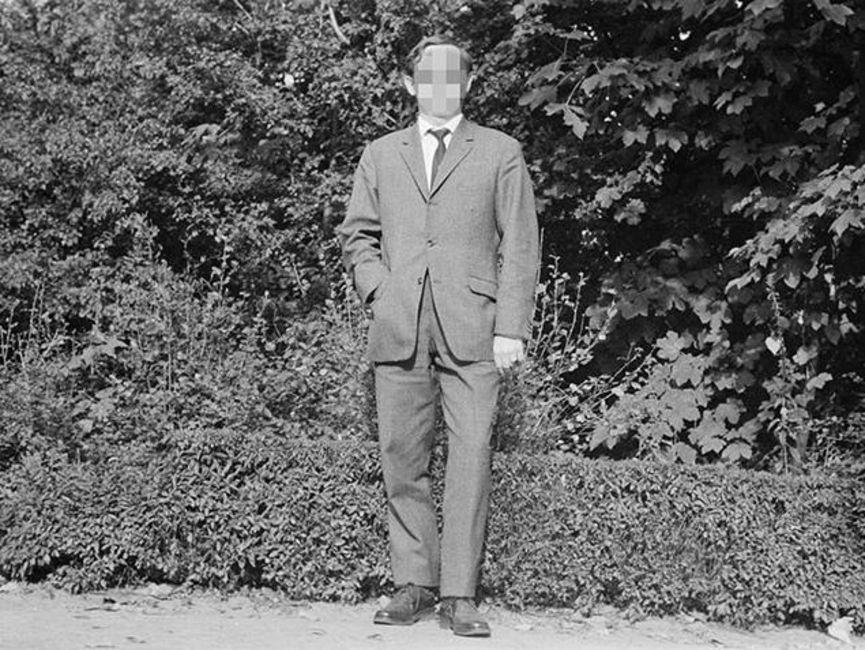 Es handelt sich um ein schwarz-weißes Lichtbild. Die Frontalaufnahme zeigt einen Mann im Anzug vor einer Hecke.