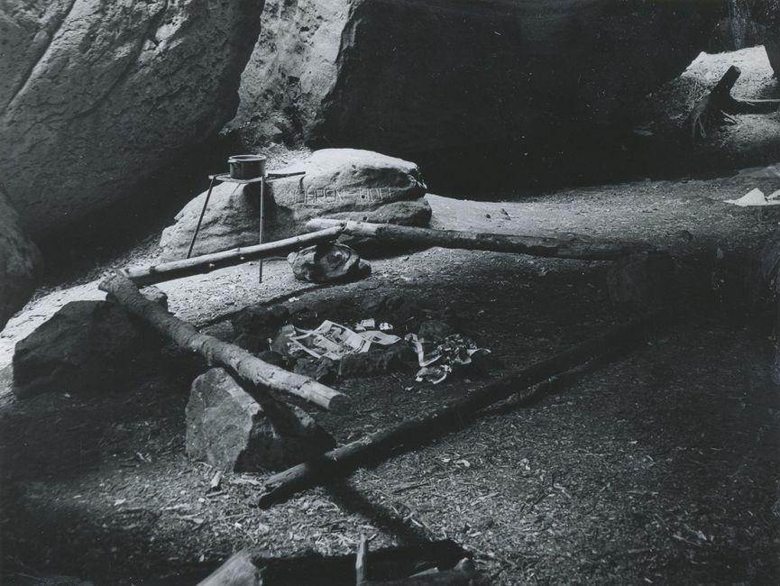 Das Bild ist eine Schwarzweißaufnahme vom Inneren der Boofe unterhalb der Felswand. Zu sehen ist eine Feuerstelle, umrandet von vier länglichen, auf Felsbrocken liegenden Baumstämmen, die ein Viereck bilden. Dahinter steht an einen größeren Gesteinsbrocken gelehnt ein Tisch, auf dem ein Topf steht. In das Gestein sind zwei unleserliche Worte geritzt.
