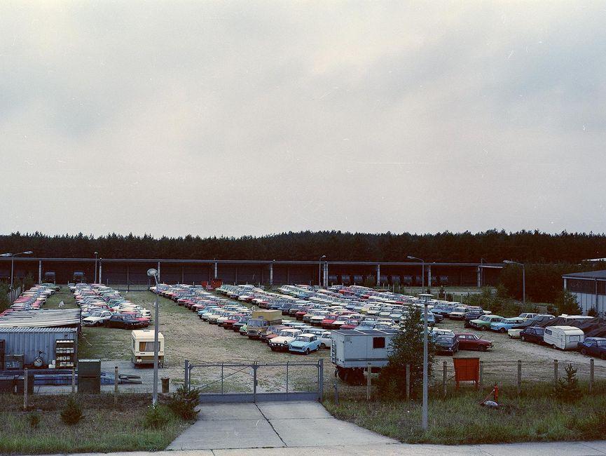 Das Bild zeigt einen großen Platz, der fast vollständig it in Reihe aufgestellten Autos gefüllt ist.
