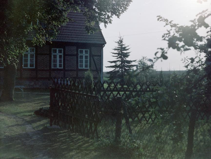 [Blick von der Auffahrt auf Hausecke und begrüntes Grundstück. Im vorderen Bildgrund des Farbfotos ist ein Jägerzaun zu sehen.]