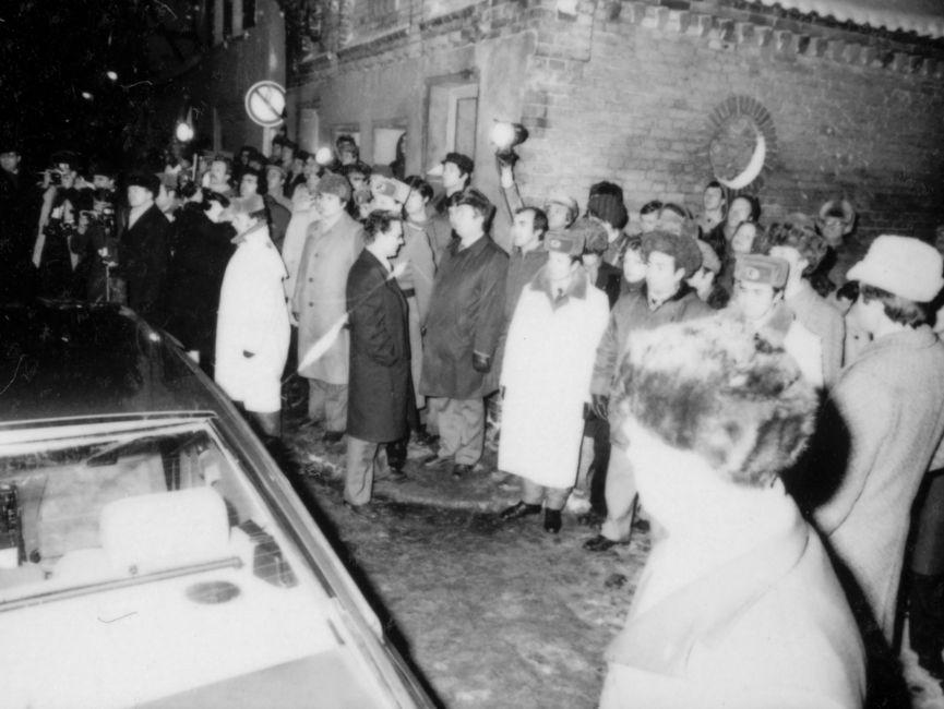Die Schwarzweißaufnahme zeigt Zuschauer und Presse am Straßenrand bei Helmut Schmidts Staatsbesuch in der DDR 1981. Die Leute von der Presse richten ihre Kamera auf die Straße, auf der ein fahrendes Auto am linken Bildrand erkennbar ist.