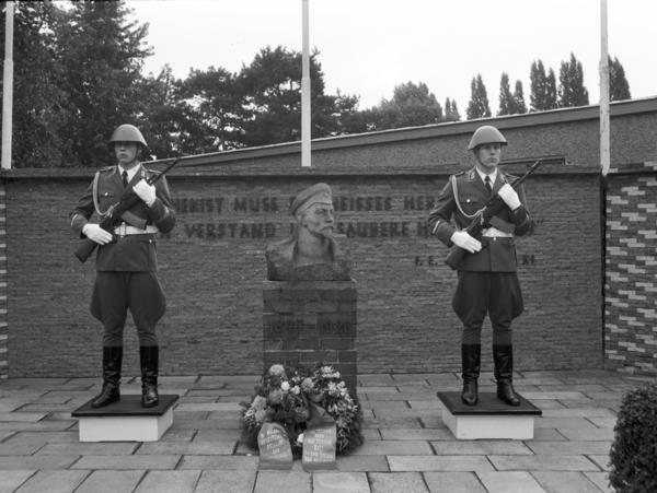 Schwarzweiß Aufnahme der Ehrenwache 1987 am Dzierzynski-Denkmal in der Kaserne des Wachregiments in Adlershof; links und rechts vom Denkmal steht ein Soldat mit Gewehr; vor dem Denkmal liegt ein Blumenkranz.