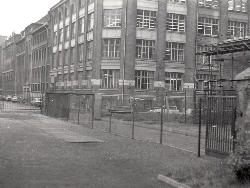 [Von einem eingezäunten, ebenmäßigen Gelände aus wurde eine Straßenecke fotografiert. Dabei stören mehrere Zäune das Blickfeld. Auf der anderen Straßenseite ist ein Altbau mit runder Ecke, auf beiden Straßenseiten parken Autos. Auf dem rechts angrenzenden Grundstück steht ein Gerüst an einem Backsteingebäude. Das Fotonegativ ist schwarzweiß.]