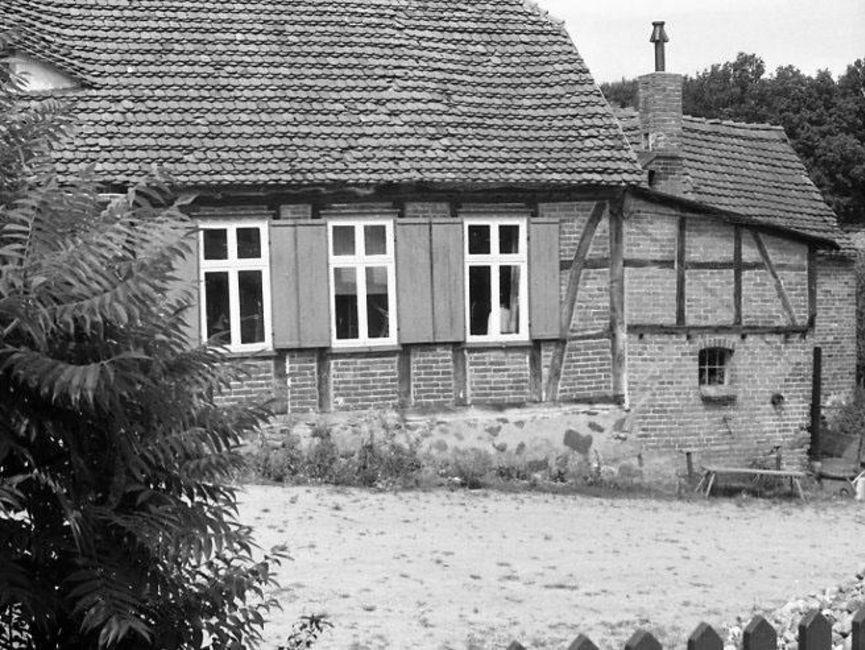 Gezeigt wird ein schwarz-weißes Lichtbild. Über den Zaun hinweg wurde in den unbefestigten Innenhof fotografiert. im Fokus steht dabei die lange Seite eines Fachwerkhauses, von dem drei Fenster gut zu sehen sind.