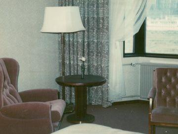 Die vorliegende Farbfotografie zeigt den Innenraum eines Hotelzimmers. Ein rechts oben im Bild befindliches Fenster zeigt eine Grünanlage und ein entfernt sichtbares Gebäude. Im Fokus steht eine kleine Garnitur bestehend aus einem roten Sessel, einem dunklen Holztisch und einer Stehlampe. Rechts und links davon steht jeweils ein gepolsterter Stuhl. Im Vordergrund, in den Raum hineinragend, befindet sich ein Einzelbett. Der Raum ist mit braunem Teppich ausgelegt, in einem hellen Muster tapeziert und die Fenster mit gemusterten sowie weißen Vorhängen versehen.