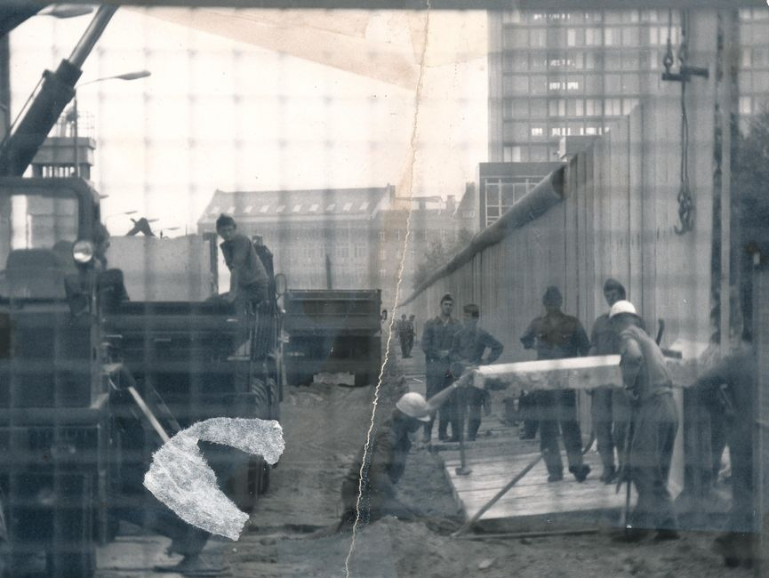 Das schwarz-weiße Lichtbild ist durch die Maschen eines Bauzauns aufgenommen worden. Mit Blick in den Ostteil der Stadt wurden die Bauarbeiten an der Berliner Mauer dokumentiert. Es stehen mehrere uniformierte Männer um zwei Bauarbeiter herum, während ein Mauerstück mittels Kran abgesenkt wird. Das Foto war mittig zerrissen worden und ist nun manuell rekonstruiert.