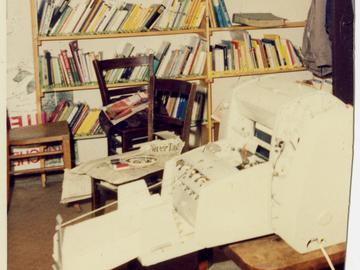 Zerschnittenes Foto einer Druckmaschine im Keller der Umweltbibliothek vor einem Bücherregal.