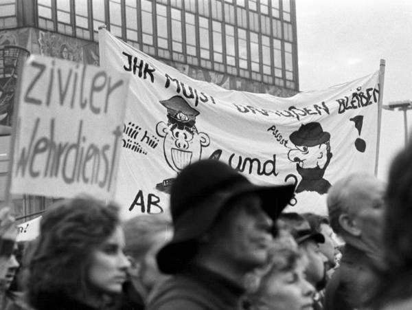 Detailaufnahme einiger Personen, die an einem Demonstrationszug am Berliner Alexanderplatz teilnehmen. Im Vordergrund ein Mann mit Hut und eine Frau, dahinter ein kleines Transparent mit der Aufschrift 'ziviler Wehrdienst'. Dahinter befindet sich ein größeres Plakat mit der Aufschrift 'Ihr müßt draußen bleiben' und Zeichnungen, die auf einen Volkspolizisten und einen Stasi-Mitarbeiter anspielen.