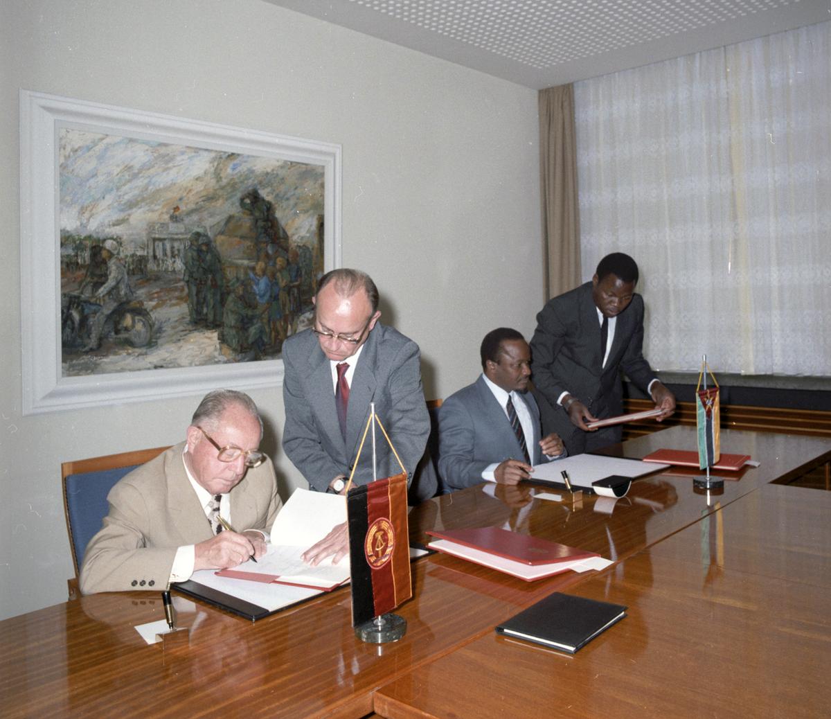 [Das farbige Lichtbild zeigt eine feierliche Unterzeichnung. Hinter einem langen Tisch sitzen Mariano de Araujo Matsinha, der mosambikanische Sicherheitsminister, und links von ihm Erich Mielke, der gerade dabei ist, ein Schriftstück zu unterschreiben. Rechts neben jedem steht jeweils ein Vertrauter, der die zu unterzeichnenden Unterlagen reicht. Vor den Ministern stehen Wimpel der Flaggen des vertretenen Landes.]