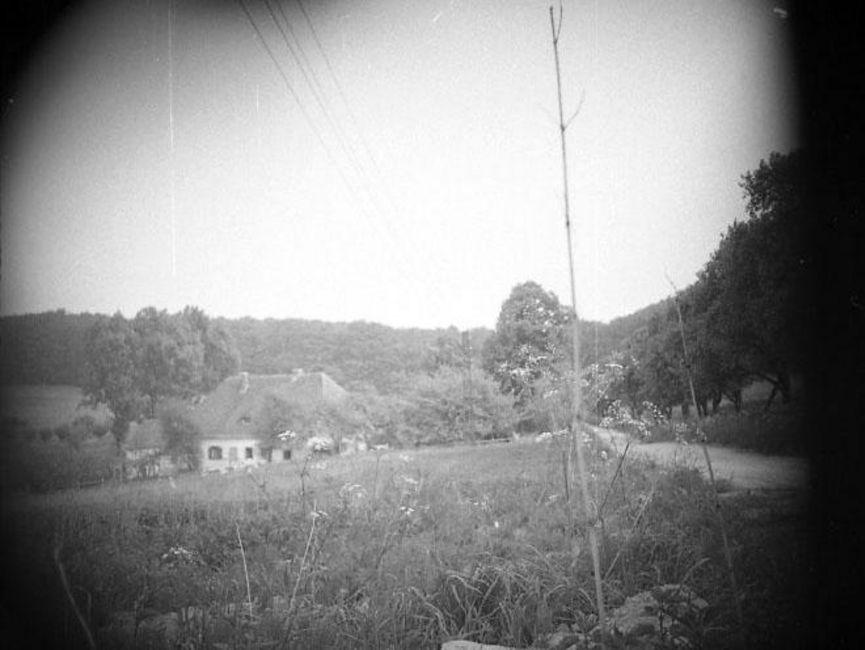 Auf dem schwarz-weißen Lichtbild ist eine hügelige Landschaft abgebildet, im Hintergrund grenzt sie an einen Waldrand. Im Mittelgrund steht ein Haus, umgeben von einigen kleineren Laubbäumen. Die Ecken sind abgedunkelt, vermutlich wurde das Foto verdeckt aufgenommen.